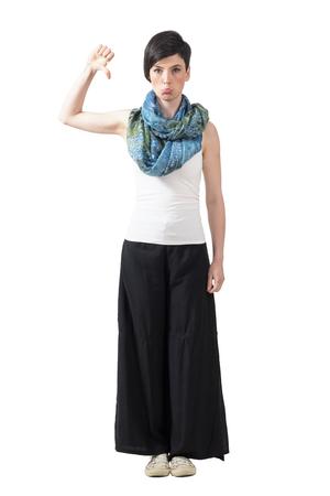 pantalones abajo: Mujer de moda de mal humor en los pantalones de pierna ancha y pañuelo para el cuello con gesto de pulgar hacia abajo. la longitud del cuerpo Retrato completo aislado sobre fondo blanco del estudio.