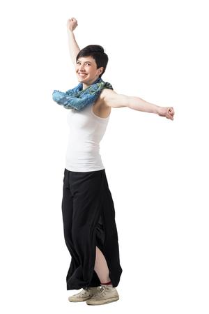 Fröhlich aufgeregte Frau Spinnen mit erhobenen Armen weiten Hosen und Schal. Ganzkörper-Länge Portrait über weißem Hintergrund Studio isoliert.