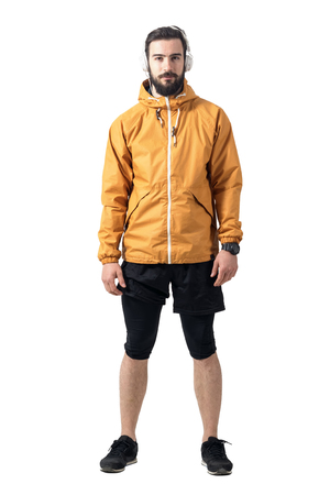male athlete: Young bearded jogger in sportswear wearing ocker jersey jacket with headphones looking at camera. Full body length portrait isolated on white background.