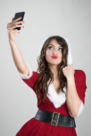Pretty Santa girl taking selfie from above in hooded Christmas costume over gray studio background.
