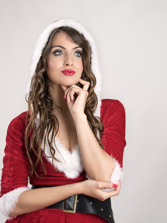 mrs  santa claus: Pensive thinking young Santa woman looking up with hoodie over gray studio background. Stock Photo