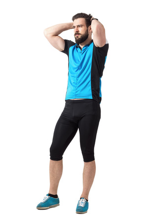 hombre deportista: Unhappy facial expression of young male cyclist with hands on head.  Full body length portrait isolated over white studio background. Foto de archivo