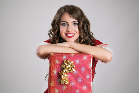 mrs santa claus: Gorgeous Santa girl resting on the big red gift box with golden ribbon looking at camera over gray studio background. Stock Photo