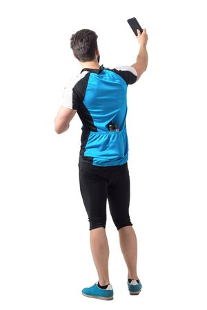studio picture: Rear view of cyclist in jersey shirt with water bottle in back pockets taking picture with smart phone.  Full body length portrait isolated over white studio background. Stock Photo