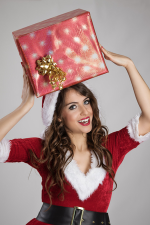 mrs  santa claus: Young Santa helper girl carrying big present package on her head over gray studio background.