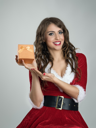mrs santa claus: Smiling happy Santa girl showing Christmas present in small golden box with ribbon over gray studio background.