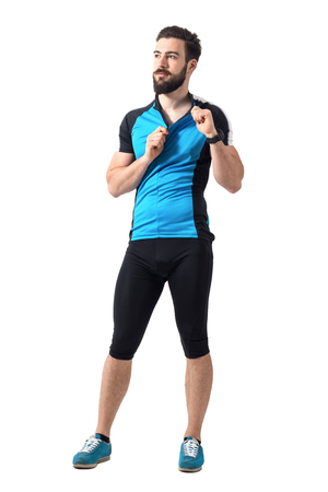 cut off: Tired young cyclist unzipping his sports cycling jersey t-shirt.  Full body length portrait isolated over white studio background. Stock Photo