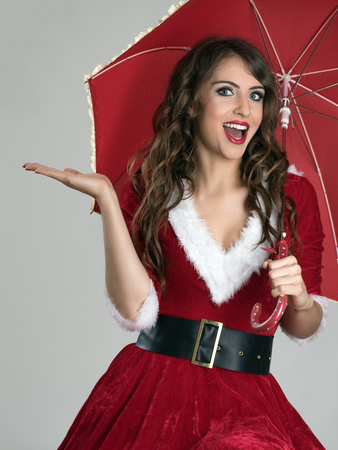 Excited Santa helper girl under umbrella with open palm over gray studio background.