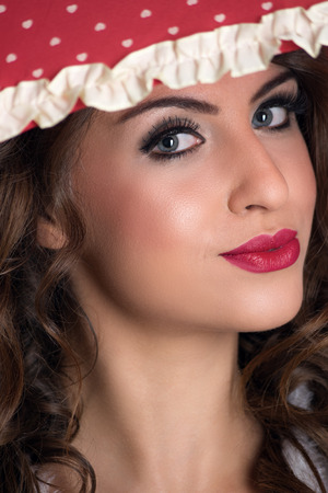 Close up portrait of young beauty woman under umbrella with red lipstick looking at camera