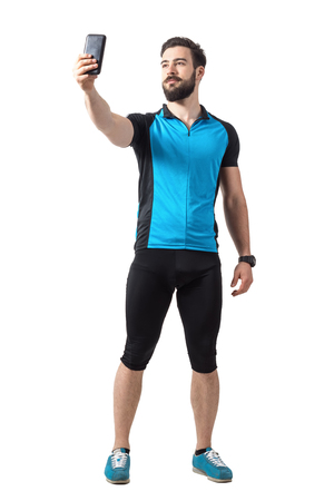 Young successful cyclist taking selfie photo with phone looking up. Front view.  Full body length portrait isolated over white studio background.