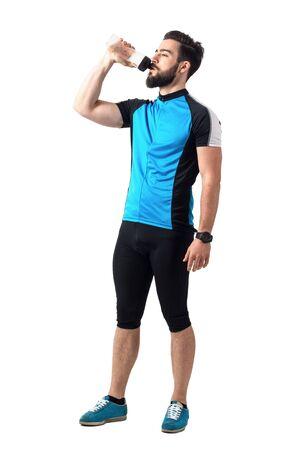 ropa deportiva: Atleta agotado en bicicleta de agua potable de ropa deportiva de la botella plástica. la longitud del cuerpo Retrato completo aislado sobre fondo blanco del estudio.