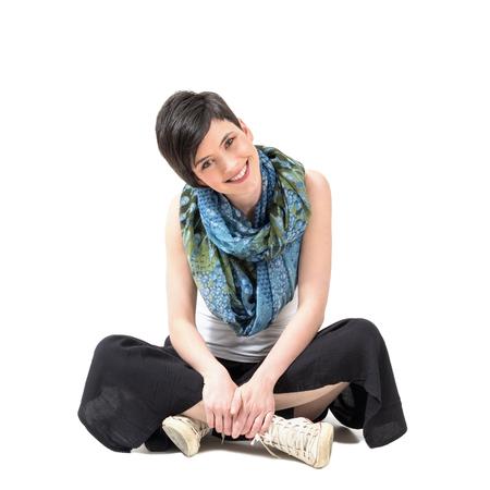 crosslegged: Charming pretty girl sitting cross-legged smiling at camera with slanted head over white studio background. Stock Photo