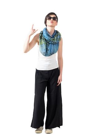 rocker girl: mujer de pelo corto con gafas de sol y bufanda que muestran los cuernos del diablo muestra de la mano. la longitud del cuerpo Retrato completo aislado sobre fondo blanco del estudio.