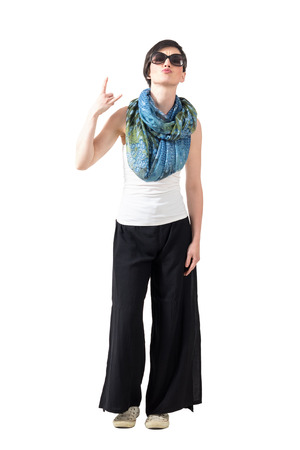 Short hair woman with sunglasses and scarf showing devil horns hand sign. Full body length portrait isolated over white studio background.