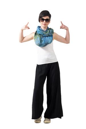 rocker girl: chica del eje de balancín con gafas de sol que muestran los cuernos del diablo rock-and-roll con las dos manos. la longitud del cuerpo Retrato completo aislado sobre fondo blanco del estudio.