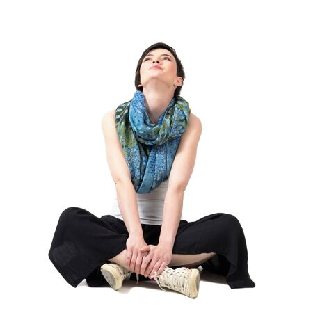 woman looking: Short hair beauty with headscarf sitting cross-legged and looking up isolated over white studio background.