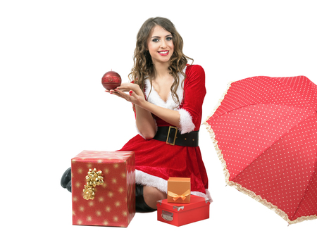Santa woman sitting and holding candle with umbrella and gift boxes isolated over white background.