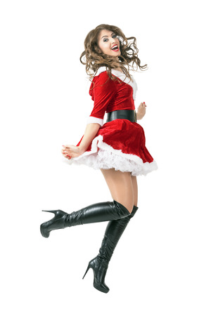 mid air: Joyful Santa girl jumping in mid air. Full body length portrait isolated over white studio background. Stock Photo