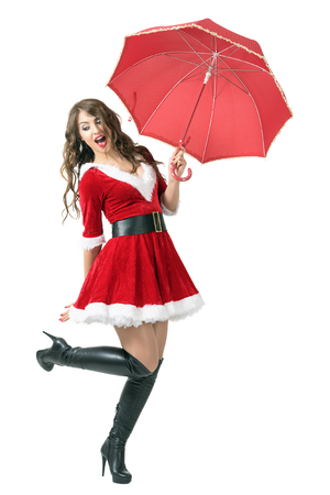 Joyful Santa woman holding umbrella jumping in mid air. Full body length portrait isolated over white studio background.