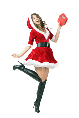 mrs santa claus: Mid air motion of jumping excited Santa woman holding gift box. Full body length portrait isolated over white studio background.
