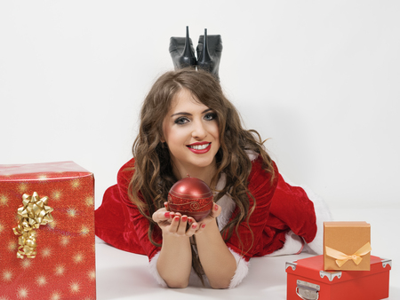 prone: Happy Santa Clause woman holding sphere candle lying prone between gifts over gray studio background.