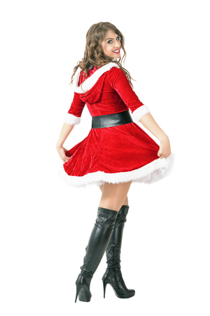 Rear view of Santa girl spinning and turning head to camera. Full body length portrait isolated over white studio background.