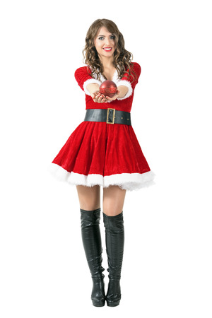 mrs santa claus: Cheerful friendly Santa Claus girl giving round sphere shaped candle at camera. Full body length portrait isolated over white studio background.