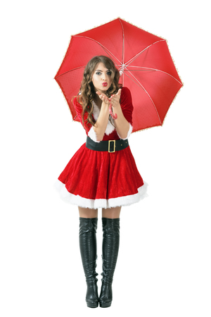 Santa woman under umbrella blowing air kiss at camera. Full body length portrait isolated over white studio background.