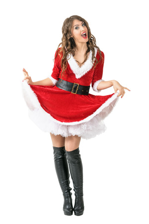 Playful merry Santa woman lifting dress looking at camera. Full body length portrait isolated over white studio background.