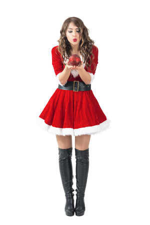 Young Santa girl blowing round decorative candle. Full body length portrait isolated over white studio background. Stock Photo