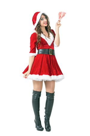 mrs  claus: Beautiful woman in Santa Claus costume holding pink duster brush smiling at camera. Full body length portrait isolated over white studio background.