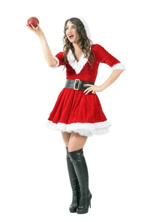 mrs santa claus: Excited Santa girl holding sphere red candle looking away with open mouth. Full body length portrait isolated over white studio background.