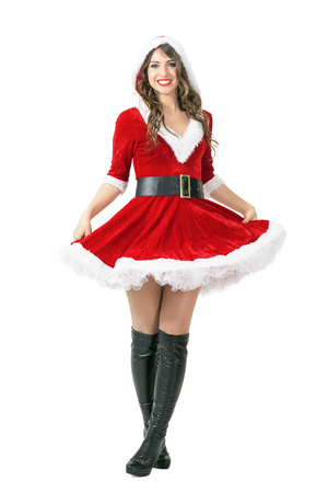 cross legs: Excited happy Santa woman standing with crossed legs and holding dress. Full body length portrait isolated over white studio background. Stock Photo