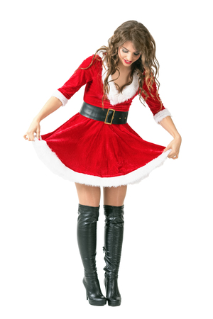 Smiling playful Santa girl lifting dress looking down. Full body length portrait isolated over white studio background.