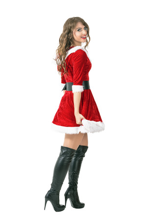 mrs santa claus: Side view of sexy Santa girl walking away turning head and smiling to camera. Full body length portrait isolated over white studio background.