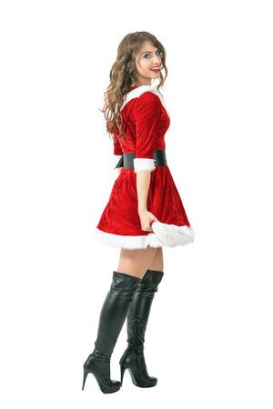 botas de navidad: Vista lateral de la muchacha atractiva de Santa alejarse girando la cabeza y sonriendo a la cámara. la longitud del cuerpo Retrato completo aislado sobre fondo blanco del estudio.