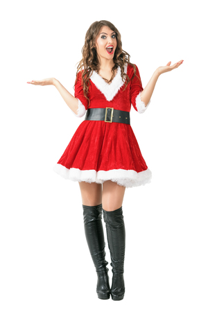 spreading arms: Astonished Santa woman spreading arms looking at camera. Full body length portrait isolated over white studio background. Stock Photo