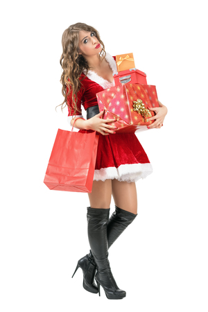 Tired Santa woman carrying many gift boxes looking at camera. Full body length portrait isolated over white studio background. Stock Photo