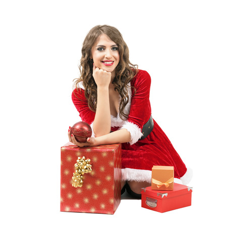 Smiling Santa woman sitting with head resting on hand around gift boxes isolated over white background. Stock Photo