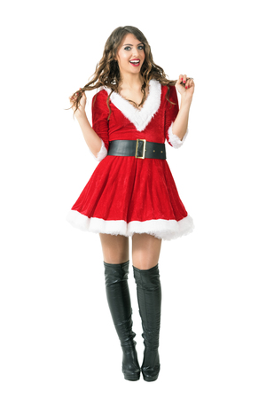 Playful excited Santa girl holding hair smiling and looking at camera. Full body length portrait isolated over white studio background.