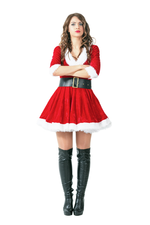 Serious annoyed Santa Claus woman standing with crossed arms looking at camera. Full body length portrait isolated over white studio background. Stock Photo