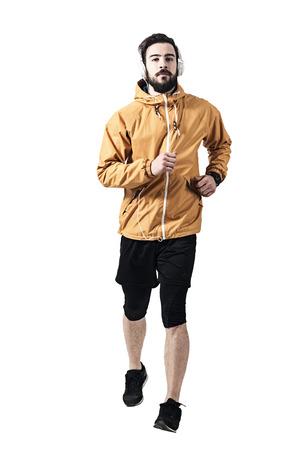 Entschlossener junger Jogger in Jacke mit Kopfhörern in Richtung Kamera. Getontes entsättigtes ganzes Körperlängenporträt lokalisiert auf weißem Studiohintergrund. Standard-Bild