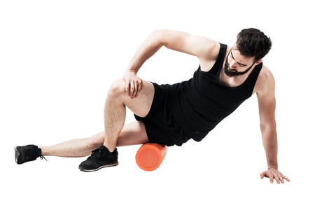 Athlete massaging and stretching iliotibial band muscle with foam roller. Full body length portrait isolated on white studio background. Stock Photo