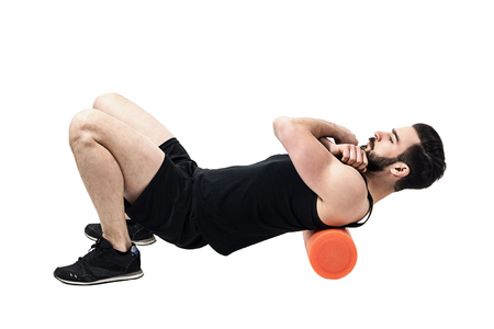 Athlete massaging upper back muscles with foam roller. Full body length portrait isolated on white studio background.