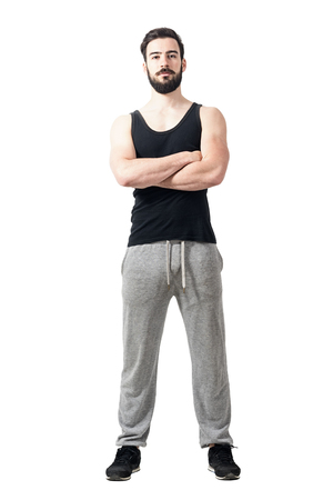 young male model: Front view of muscular fitness athlete with crossed arms. Toned desaturated full body length portrait isolated on white studio background.