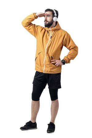 sportsman: Deportista joven en la chaqueta con los auriculares que cubre los ojos de la luz solar que mira a la distancia. longitud de cuerpo completo retrato aislado en el fondo blanco del estudio. Foto de archivo