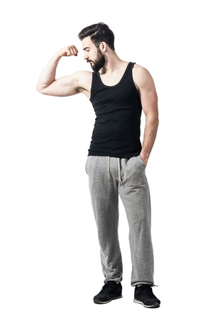 Athlete in black tank top flexing arm biceps looking at muscles. Toned desaturated full body length portrait isolated on white studio background.