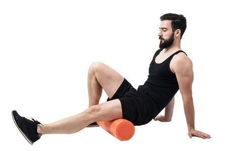 Athlete massaging and stretching legs calf muscles with foam roller. Full body length portrait isolated on white studio background.