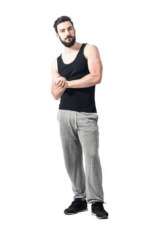 clasped hands: Skeptical athlete in sportswear with clasped hands looking at camera. Toned desaturated full body length portrait isolated on white studio background.