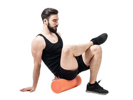Athlete massaging glutes muscles with foam roller. Full body length portrait isolated on white studio background.